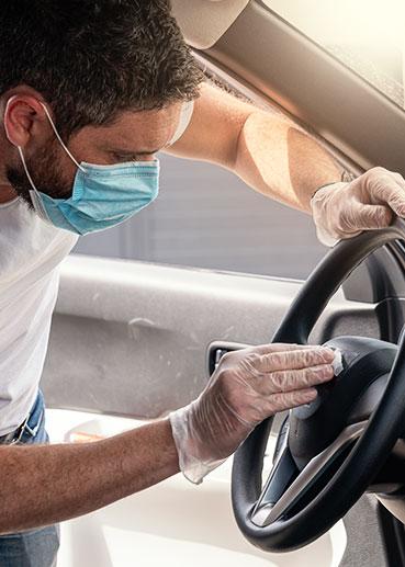 Mitarbeiter bei Fahrzeugdesinfektion